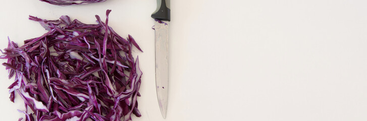 Top view of red sliced cabbage and a knife on white background. Healthy eating concept with space for text
