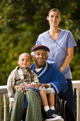 Senior man in a wheelchair with his grandson sitting on his lap and a female nurse standing behind them pose for a portrait on a porch.