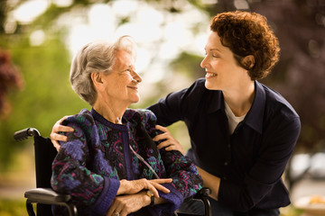 Mature woman leans over to smile and talk to a senior woman with a oxygen nose hose (cannula) sitting in a wheelchair outside.