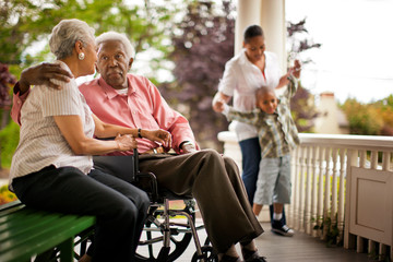 Senior man speaking with his wife on a porch.