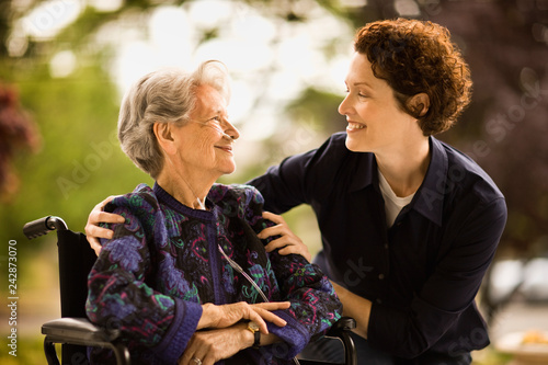 Mature woman leans over to smile and talk to a senior woman with a ...