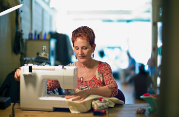 Mature female dressmaker making clothes while sitting at a sewing machine inside her store.