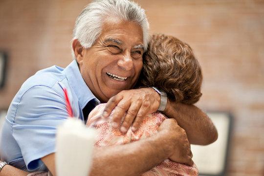 Smiling senior man happily embracing his wife.
