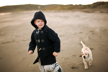 Preschool age boy running with his puppy on the beach.