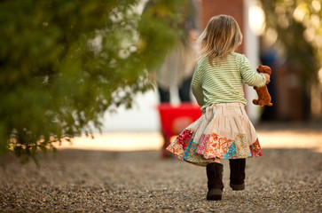 Rear view of young girl walking, holding her soft toy.