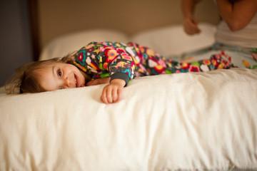 Smiling toddler girl lying on bed in pajamas.