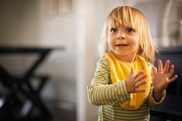 Portrait of baby girl wearing a yellow bib.