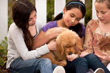 Three girls sitting with puppy.