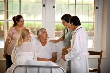 Elderly man receiving a hospital visit from his family.