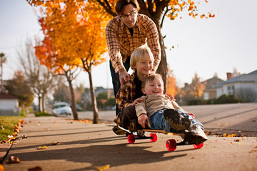Father pushing boys on skateboard