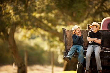 Two young brothers sitting on the back of a pick-up truck in the country and laughing