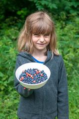 kleines Mädchen mit Blaubeeren
