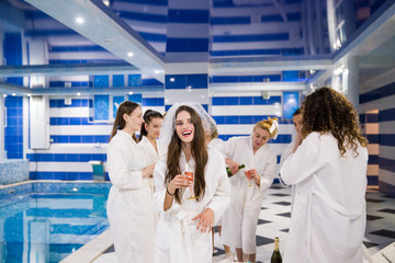 The beautiful smiling bride standing near her friends at the hen party near a pool and holding a glass of champagne