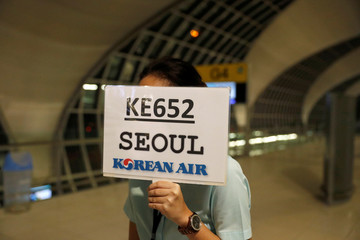 Woman holds a sign for Korean Air flight KE652 at Bangkok Airport