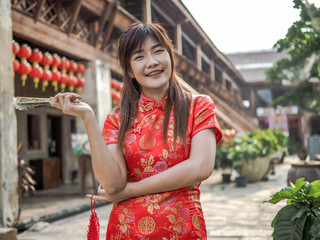 Beautiful young woman smile wear cheongsam deep red dress holding a fan looking camera. Chinese New Year