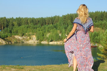 Summer holidays concept. Young happy girl in waving dress and flying scarf admires a landscape of the summer lake.