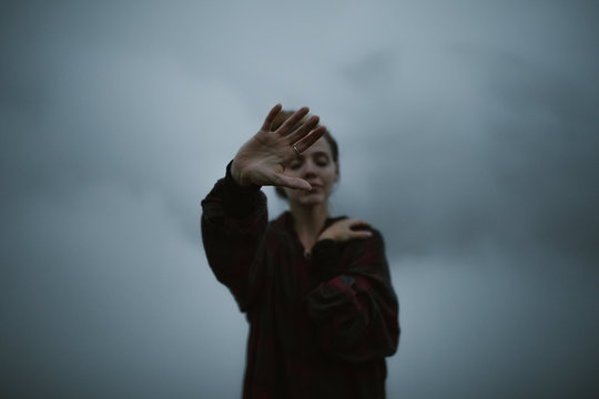 woman's hands in the clouds moody and dark