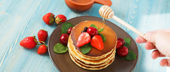 pancakes in a plate with strawberries, mint, honey and cherry on a bright blue background.