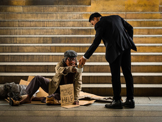 A businessman gives smartphone to a homeless man sitting on a ladder