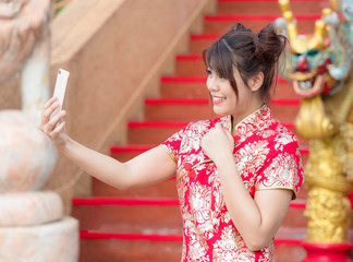 Asian beautiful girl dressed in Chinese national costume is taking pictures