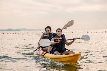 two asian girls in kayak on the ocean by Thailand