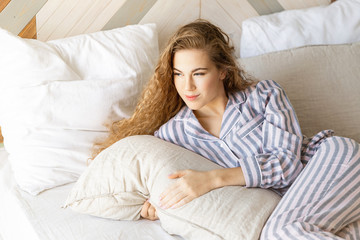 Portrait of lovely young woman laying in bedroom and enjoying good morning. Attractive girl with long wavy hair in striped pyjamas. Sweet home and happiness concept