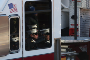 Firefighters are seen reflected during the funeral procession for New York City fire department firefighter Steven Pollard of Ladder 170 at Good Shepherd church in the Brooklyn borough of New York City