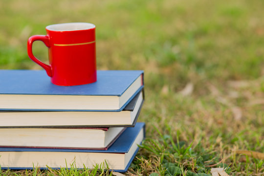 Cup of coffee with pile of closed books outside.