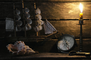 Marine ship, compass, seashell and burning candle on captain table. Sea travel background. Pirate concept.