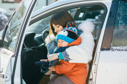 Young mother on driver's seat of car and trying to wear mittens her cute crying toddler son in cold winter day. Family wearing in bright warm clothes.