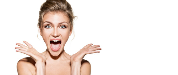Portrait of surprised pretty blonde model overwhelmed with emotions. Astonished woman posing in studio on white background. Beauty and surprise concept