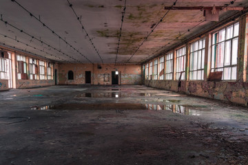 Shabby interior with big windows and reflections in  the puddles on the floor inside the abandoned factory building
