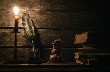 Quill pen in a inkpot, dragon statuette and stack of books in the light of burning candle on the writer desk background. Education concept.