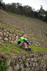 a man sits on a terraced hill