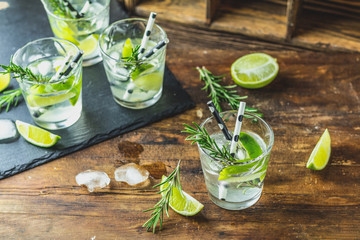 Fresh cocktail with lime, ice and rosemary, mojito cocktail in a bur on a rustic table