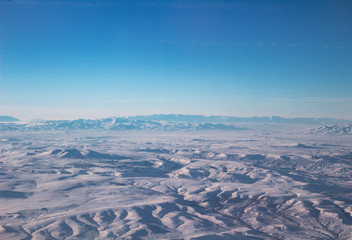 The sky with clouds and mountains in snow. Photo taken from an airplane.