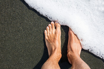Male feet on the black volcanic sand covers with white sea foam. Minimalism. Geometric. Diagonal