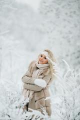 Portrait of blonde woman on walk in winter forest