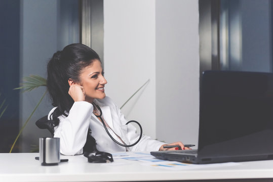 Female doctor searching online on laptop