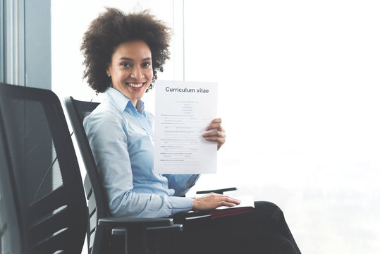 Businesswoman looking at camera and showing her cv