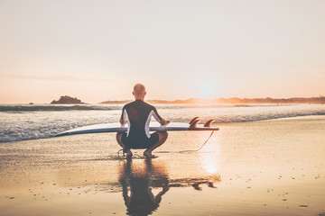 Surfer man with long board surf sitting on the sandy ocean beach and enjoying the sunset sky. Never ending summer surfing concept image.