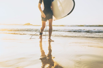 Surfer man with long board walking out fro sea waves on sunny ocean beach. Active vacation spending time concept image.