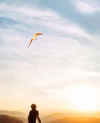 Man starting to fly bright kite in sunset sky over the mountain. Successful startup concept image.