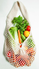 Assorted vegetables in mesh grocery bag isolated on white background