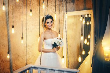 Young happy bride n the room with a lot of light bulbs