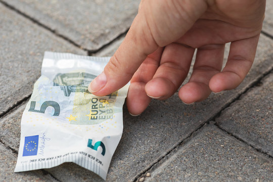 Woman is picking five euro banknote from the ground