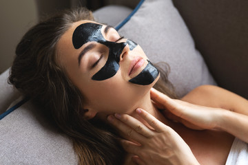 Beautiful woman is relaxing at home with black peel-off mask on her face