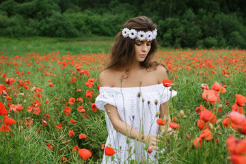 Beautiful woman in field with a lot of poppy flowers