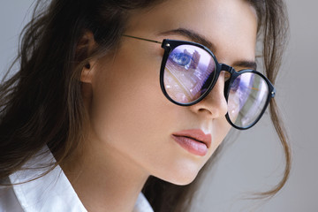 Close up portrait of Young woman with a reflection of modern city inside eyeglasses