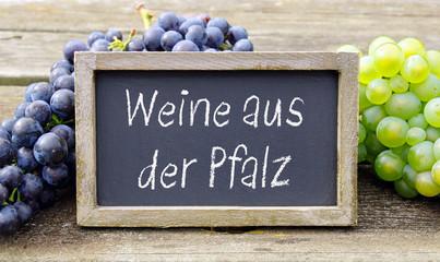 Weine aus der Pfalz, Kreidetafel mit Text und Weintrauben auf altem Holztisch